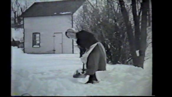 Grandma in sun-bonnet shoveling snow in Pennsylvania, 1950s