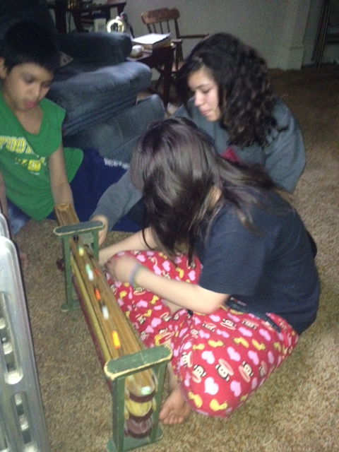 Gloria's grand-children playing with the same marble-roller we had as children: Demetri 12, Inani 13, and Samantha 10.