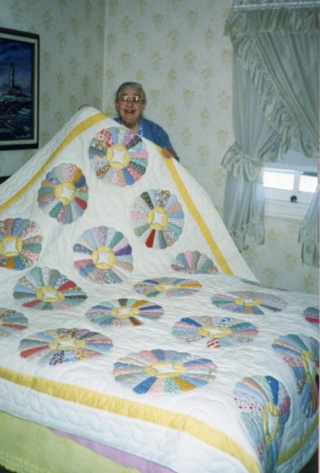 1999_0900_Mother L_holding up white quilt w circles