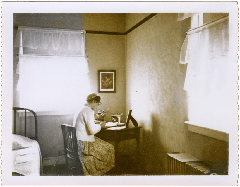 Filmy, white curtains filter pure, virginal light into this teacher's dorm room study