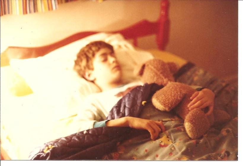 Joel sleeping with teddy bear, age 8